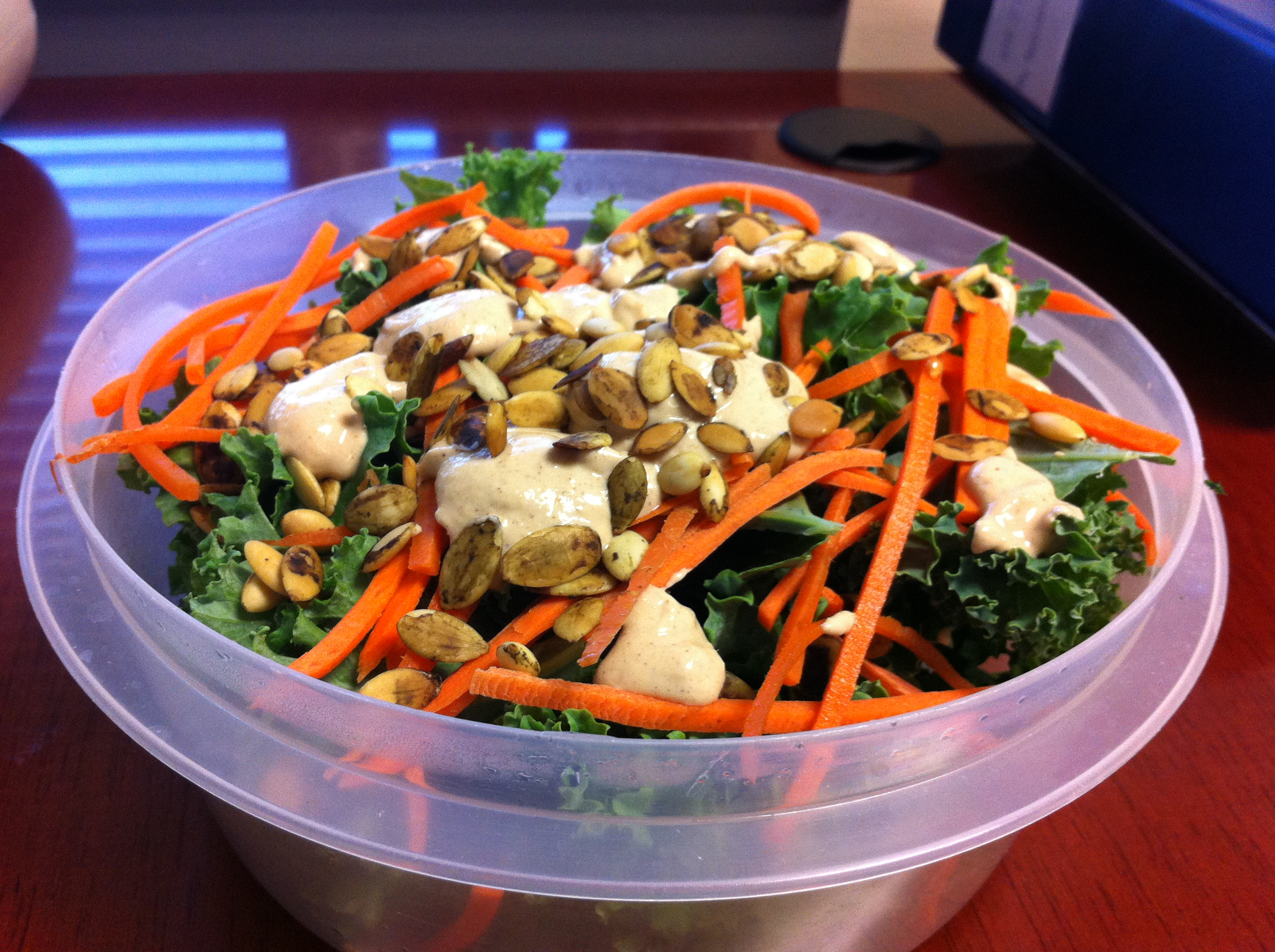 A big bowl of kale with shredded carrots, pumpkin seeds, and my favorite sesame mustard dressing.